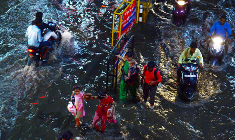 Commuters make their way through a flooded street after heavy rains in Allahabad on August 13, 2019.