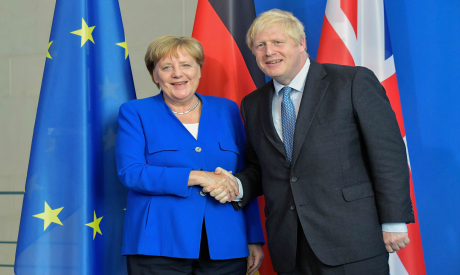 German Chancellor Angela Merkel and British Prime Minister Boris Johnson shake hands on August 21, 2