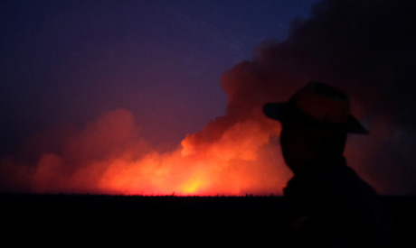 A man is seen on a burning tract of the Amazon jungle in Canarana, Mato Grosso state, Brazil August
