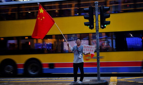 A lone pro-government supporter waves a China flag near Central in Hong Kong (AFP)