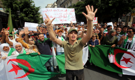 Demonstrators shout slogans and carry national flags during a protestin Algiers