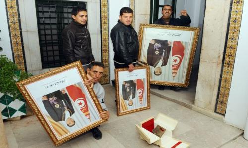 Tunisian employees remove portraits of Ben Ali