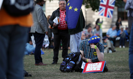 An anti-Brexit protester sits with a placard outside the Houses of the Parliament in London, Britain