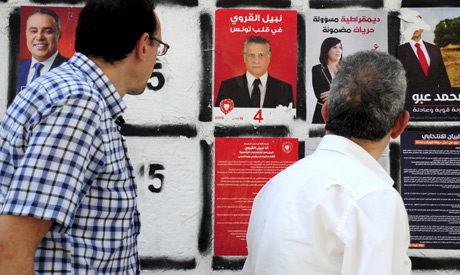 Men watch a campaign poster of the owner of the Tunisian private channel Nessma TV, Nabil Karoui, ce