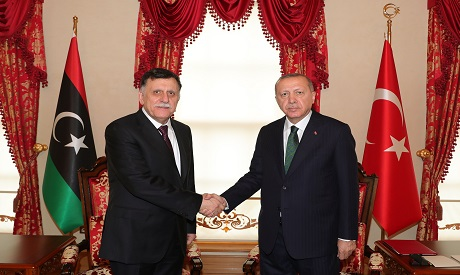 Erdogan (R) shakes hand with Fayez al-Sarraj (L)