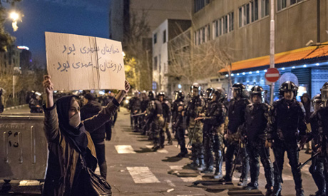 """An Iranian woman holds a placard reading in Farsi """"Your mistake was unintentional, your lie was inte"""