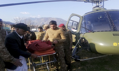 Pakistan army soldiers transport an injured victim of an avalanche