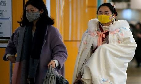 Women wearing protective masks are seen at a subway station in Shanghai