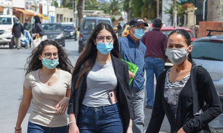 Tunisians wearing masks amid COVID-19 pandemic walk by on a street in Tunis . AFP