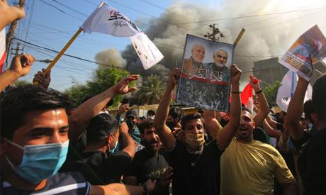 Iraqi demonstrators, supporters of the Hashed al Shaabi, raise portraits of slain Iranian commander