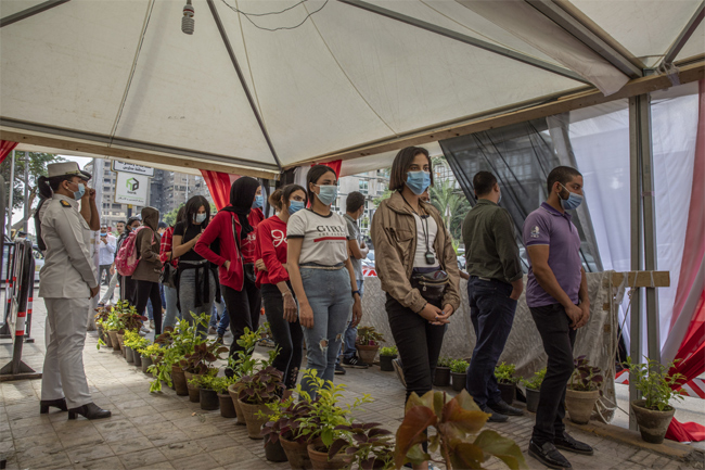 People wait in line on the first day of the parliamentary election outside a polling station in Giza
