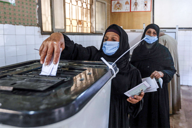 A woman, mask-clad due to the COVID-19 coronavirus pandemic, casts her ballot at a polling station i