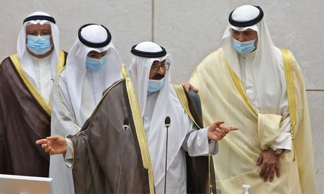 The new Kuwaiti crown prince Sheikh Meshal al-Ahmad al-Jaber Al-Sabah (C) gestures as he takes the o