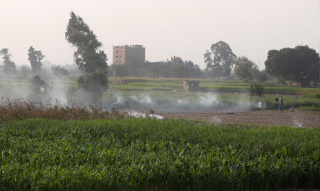 A destructed house is seen surrounded by fields while a farmer burns straw along the agricultural ro