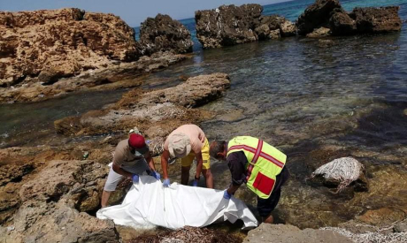 Rescue workers recover the dead bodies of migrants