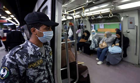 Police officer wearing a protective face mask checks passengers inside a train at the underground Al