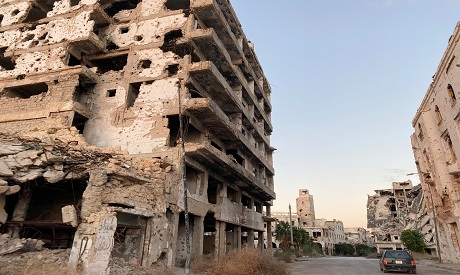 A car is seen between destroyed buildings in Benghazi REUTERS