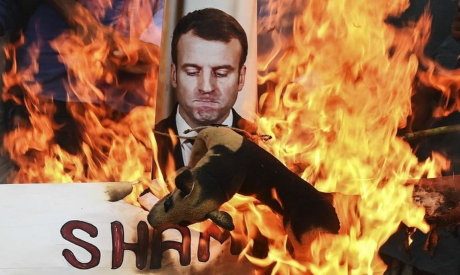 Protesters burn a photo for  French President Emmanuel Macron