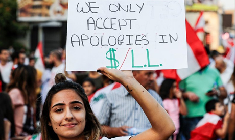 File Photo: A Lebanese woman holds up a sign demanding that the country