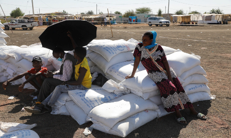 Ethiopian refugees sit on bags of food aid
