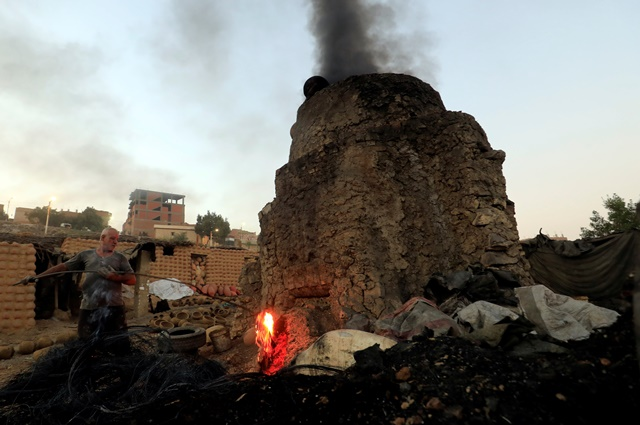 Egyptian potter Hosni Hussien, whose sons are also potters, heats the mud oven at El Nazla village i