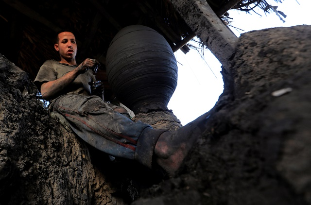 An Egyptian potter works with mud to make traditional shapes of pottery at El Nazla village in Fayou