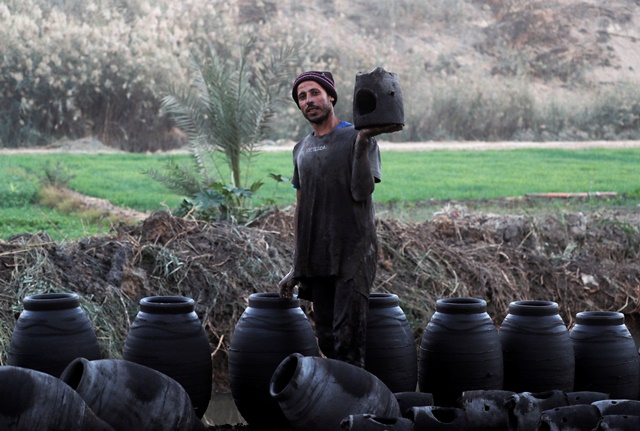 Alaa Ahmed, a 31-year-old Egyptian potter, shows river-clay with traditional shapes of pottery at El