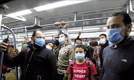 People wearing protective face masks stand inside Cairo