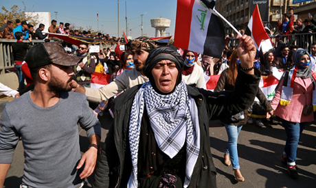 Students and other demonstrators hold national flags during a protest to condemn a militia attack on