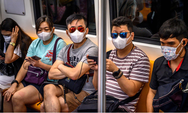 People with face masks ride a BTS Sky train in Bangkok on January 26, 2020. (Photo: AFP)
