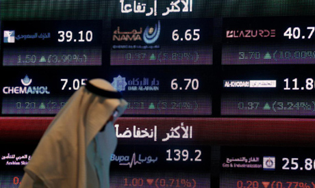An investor walks past a screen displaying stock information at the Saudi Stock Exchange (Tadawul) i