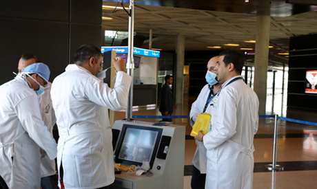 Medical staff wear protective gear before checked passengers by thermal scanners for coronavirus sym