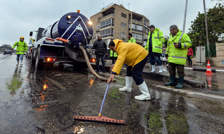 Municipal workers work on draining a street using a pump following flooding by rainwater in the Egyp
