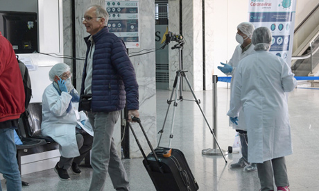 Health personnel monitor a thermal scanner as passengers arrive at Tunis-Carthage Airport in the Tun