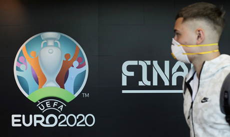 Travellers pass by a logo of the 2020 UEFA European Football Championship displayed on a wall inside