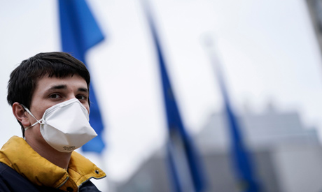 A man wearing a face mask as a preventive measure looks on in front of the EU headquarters in Brusse