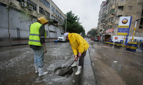 Egyptian municipal workers try to clear floodwater from a street during a thunderstorm and heavy rai