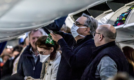 Passengers, some wearing protective face masks, aboard an EgyptAir flight (AFP)