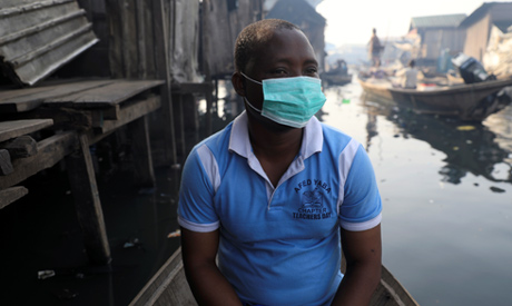 A man wearing a face mask sits in a traditional canoe at the Makoko community in Lagos, Nigeria Marc