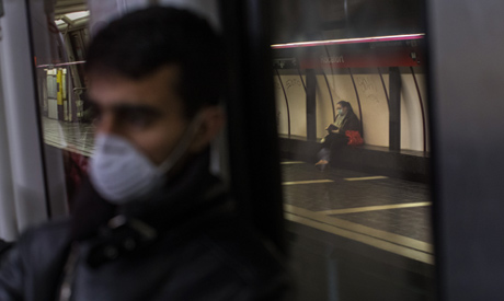 A man wearing a face mask travels by train in Barcelona, Spain, Wednesday, March 18, 2020. (AP)