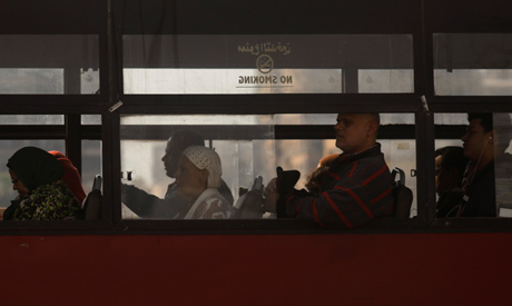 Passengers look through the windows of a bus in the Egyptian capital Cairo, Egypt