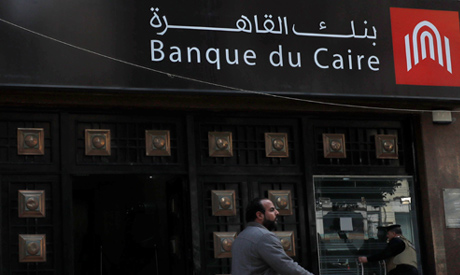A man walks in front of a branch of Banque Du Caire in Cairo, Egypt March 18, 2020. (Reuters)