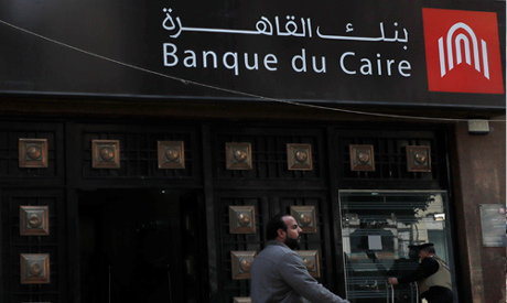 A man walks in front of a branch of Banque Du Caire in Cairo, Egypt (Reuters)