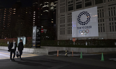 Two men walk past a large banner promoting the Tokyo 2020 Olympics in Tokyo, Tuesday, March 24, 2020