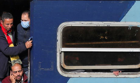 People travel on an overcrowded train befor hours of curfew which was ordered by the Egyptian Prime