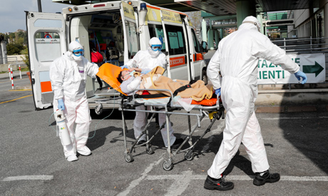 Medical workers in protective suits push a patient on a stretcher in front of the Policlinico Tor Ve