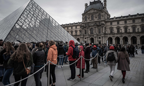 Visitors queue outside the Pyramid, the main entrance to the Louvre museum in Paris on March 4, 2020