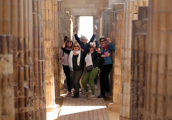 Tourists pose for a photograph at the standing step pyramid of Saqqara after its renovation, south o
