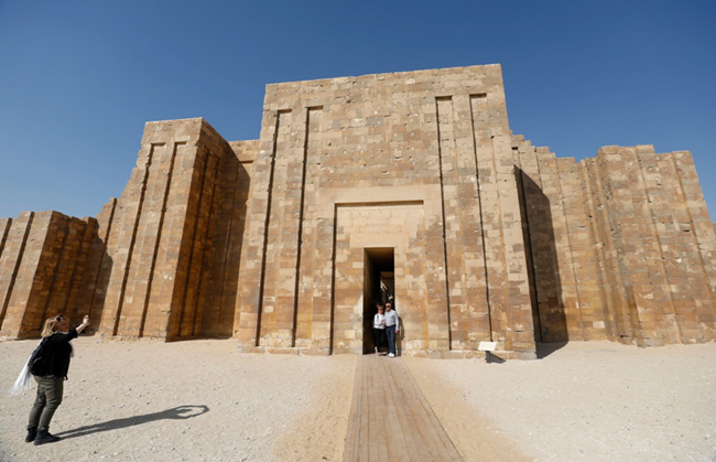 Tourists take pictures at the archaeological site of the standing step pyramid of Saqqara after its