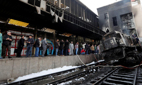 People gather at the main train station after a fire following a train crash caused deaths and injur